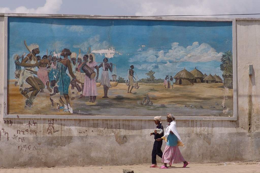 Women walk past a mural in Asmara, Eritrea